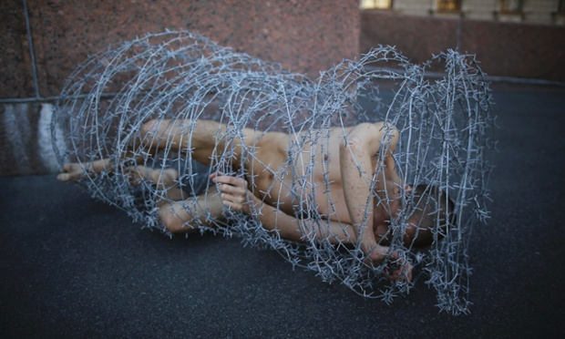 Nude artist Pyotr Pavlensky lies on the ground wrapped in a roll of barbed wire during a protest outside the city's legislative assembly